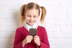 Όμορφο μικρό κορίτσι που κρατά ένα τηλέφωνο και που γράφει το μήνυμα Στοκ φωτογραφία με δικαίωμα ελεύθερης χρήσης