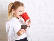 Όμορφο μικρό κορίτσι που κρατά ένα τηλέφωνο και που πίνει το τσάι Στοκ Εικόνες
