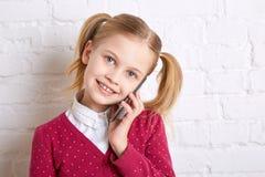 Όμορφο μικρό κορίτσι που κρατά και που μιλά ένα τηλέφωνο Στοκ Φωτογραφία