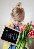 Όμορφο μικρό κορίτσι που κρατά μια ανθοδέσμη των κόκκινων τουλιπών στοκ εικόνα με δικαίωμα ελεύθερης χρήσης