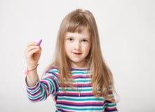 Όμορφο μικρό κορίτσι που κρατά μια πορφυρή μάνδρα πίλημα-ακρών και που σύρει το SOM Στοκ Εικόνες
