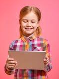 Όμορφο μικρό κορίτσι που κρατά μια ταμπλέτα και ένα χαμόγελο Στοκ φωτογραφίες με δικαίωμα ελεύθερης χρήσης
