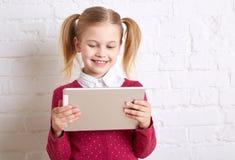 Όμορφο μικρό κορίτσι που κρατά μια ταμπλέτα και ένα χαμόγελο Στοκ Εικόνες