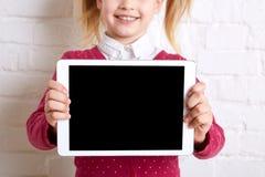 Όμορφο μικρό κορίτσι που κρατά μια ταμπλέτα στο ελαφρύ υπόβαθρο διάστημα αντιγράφων Στοκ Φωτογραφία