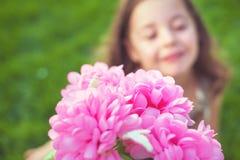 Όμορφο μικρό κορίτσι που κρατά τα ζωηρόχρωμα λουλούδια στοκ εικόνα με δικαίωμα ελεύθερης χρήσης
