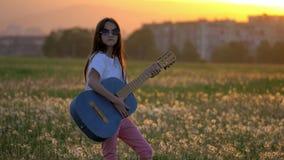 Όμορφο μικρό κορίτσι που παίζει την κιθάρα στον τομέα πικραλίδων κατά τη διάρκεια του ηλιοβασιλέματος υπαίθρια μακρυά από τις συγ απόθεμα βίντεο