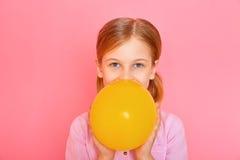 Όμορφο μικρό κορίτσι που στέκεται και που διογκώνει ένα κίτρινο μπαλόνι Στοκ Εικόνες