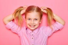Όμορφο μικρό κορίτσι που στέκεται και που κρατά ponytails στο κεφάλι της Στοκ φωτογραφίες με δικαίωμα ελεύθερης χρήσης