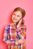 Όμορφο μικρό κορίτσι που στέκεται και που μιλά ένα τηλέφωνο στο ρόδινο υπόβαθρο Στοκ εικόνα με δικαίωμα ελεύθερης χρήσης