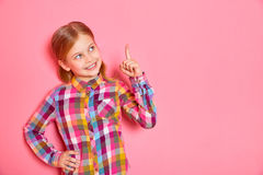 Όμορφο μικρό κορίτσι που στέκεται με το αυξημένο δάχτυλο επάνω διάστημα αντιγράφων Στοκ Εικόνα