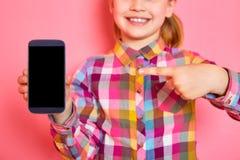 Όμορφο μικρό κορίτσι που στέκεται σε ένα ρόδινο υπόβαθρο που κρατά ένα τηλέφωνο και που παρουσιάζει ένα δάχτυλο στην οθόνη διάστη Στοκ εικόνα με δικαίωμα ελεύθερης χρήσης