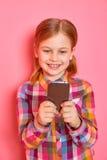 Όμορφο μικρό κορίτσι που στέκεται σε ένα ρόδινο υπόβαθρο που κρατά ένα τηλέφωνο και που παρουσιάζει ένα δάχτυλο στην οθόνη διάστη Στοκ Φωτογραφίες