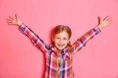 Όμορφο μικρό κορίτσι που στέκεται στο ρόδινο υπόβαθρο με τα αυξημένα χέρια επάνω Στοκ φωτογραφία με δικαίωμα ελεύθερης χρήσης