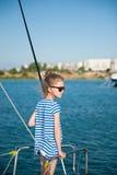 Όμορφο μικρό κορίτσι που φορά τα γυαλιά ηλίου και το ριγωτό πουκάμισο στο σκάφος στο θαλάσσιο λιμένα Στοκ εικόνα με δικαίωμα ελεύθερης χρήσης