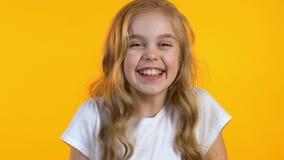 Όμορφο μικρό κορίτσι που χαμογελά ειλικρινά για τη κάμερα στο απομονωμένο φωτεινό υπόβαθρο απόθεμα βίντεο