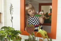 Όμορφο μικρό κορίτσι που χαμογελά στο παράθυρο σπιτιών παιχνιδιών με Thumbelina Στοκ φωτογραφίες με δικαίωμα ελεύθερης χρήσης