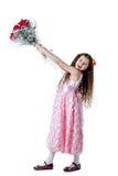 Όμορφο μικρό κορίτσι σε ένα ρόδινο φόρεμα με μια ανθοδέσμη των κόκκινων τριαντάφυλλων στοκ εικόνα