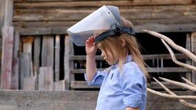 Όμορφο μικρό κορίτσι στα προστατευτικά παιχνίδια κρανών οικοδόμων ή μηχανικών έξω απόθεμα βίντεο