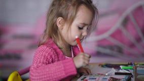 Όμορφο μικρό κορίτσι στη ρόδινη ζακέτα που σύρει την απεικόνιση με τα μολύβια στον παιδικό σταθμό Το μικρό παιδί χρωματίζει απόθεμα βίντεο