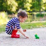 Όμορφο μικρό κορίτσι στις κόκκινες μπότες βροχής που παίζει με το λαστιχένιο βάτραχο Στοκ φωτογραφίες με δικαίωμα ελεύθερης χρήσης