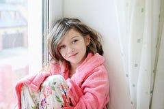 Όμορφο μικρό κορίτσι στο μπουρνούζι κοντά στο παράθυρο Στοκ Εικόνες