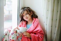 Όμορφο μικρό κορίτσι στο μπουρνούζι με το φλυτζάνι του τσαγιού Στοκ Εικόνες