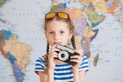 Όμορφο μικρό κορίτσι στο ριγωτό πουκάμισο ναυτικών και γυαλιά ηλίου με τον τρύγο camere στα χέρια στο υπόβαθρο παγκόσμιων χαρτών Στοκ φωτογραφία με δικαίωμα ελεύθερης χρήσης