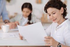 Όμορφο μικρό παιδί που διαβάζει τα πληροφοριακά τυπωμένα κείμενα Στοκ Φωτογραφία