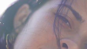 Όμορφο μισό πρόσωπο γυναικών, ελκυστικά θηλυκά σκοτεινά μάτια χαμόγελου τρίχας, ελαφριά ομίχλη ήλιων απόθεμα βίντεο