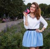 Όμορφο μοντέρνο κορίτσι με την εκλεκτής ποιότητας ρόδινη κάμερα στο πάρκο το θερμό θερινό βράδυ Στοκ Φωτογραφίες