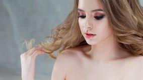 Όμορφο μοντέρνο κορίτσι, πορτρέτο με το φωτεινό μάτι makeup Μια νέα γυναίκα αγγίζει τα σκέλη της τρίχας στοκ φωτογραφία με δικαίωμα ελεύθερης χρήσης