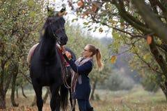 Όμορφο μοντέρνο κορίτσι σε ένα καπέλο κάουμποϋ με ένα άλογο που περπατά στο δάσος φθινοπώρου, ύφος χωρών Στοκ φωτογραφία με δικαίωμα ελεύθερης χρήσης