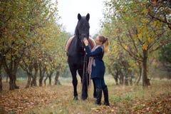 Όμορφο μοντέρνο κορίτσι σε ένα καπέλο κάουμποϋ με ένα άλογο που περπατά στο δάσος φθινοπώρου, ύφος χωρών Στοκ εικόνες με δικαίωμα ελεύθερης χρήσης