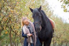 Όμορφο μοντέρνο κορίτσι σε ένα καπέλο κάουμποϋ με ένα άλογο που περπατά στο δάσος φθινοπώρου, ύφος χωρών Στοκ Εικόνες