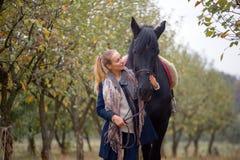 Όμορφο μοντέρνο κορίτσι σε ένα καπέλο κάουμποϋ με ένα άλογο που περπατά στο δάσος φθινοπώρου, ύφος χωρών Στοκ Εικόνα