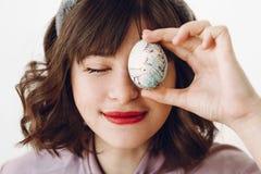 Όμορφο μοντέρνο κορίτσι στα αυτιά λαγουδάκι που κρατά το αυγό Πάσχας στα μάτια στοκ εικόνα
