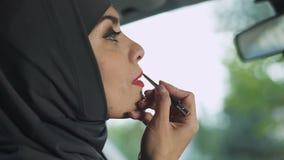 Όμορφο μουσουλμανικό θηλυκό που εφαρμόζει το σαγηνευτικό κόκκινο κραγιόν στο αυτοκίνητο, φεμινισμός απόθεμα βίντεο