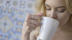 Όμορφο μπλε-eyed νέο ξανθό τσάι κατανάλωσης γυναικών r Νέα όμορφη κυρία με το δαχτυλίδι στην κατανάλωση δάχτυλών της στοκ εικόνες με δικαίωμα ελεύθερης χρήσης