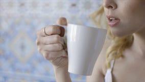 Όμορφο μπλε-eyed νέο ξανθό τσάι κατανάλωσης γυναικών r Νέα όμορφη κυρία με το δαχτυλίδι στην κατανάλωση δάχτυλών της στοκ φωτογραφία