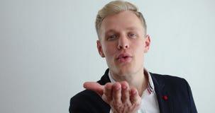 Όμορφο μπλε eyed ξανθό άτομο που στέλνει το φιλί αέρα - μορφή της καρδιάς απόθεμα βίντεο