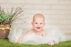 Όμορφο μπλε-eyed μωρό που βρίσκεται σε tummy του, κοντά στα αυγά Πάσχας στοκ φωτογραφία