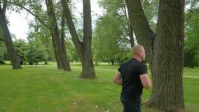 Όμορφο μυϊκό άτομο που τρέχει υπαίθρια στο πάρκο απόθεμα βίντεο