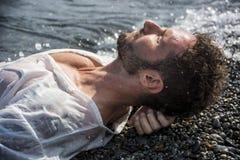 Όμορφο μυϊκό άτομο στην παραλία που βάζει στο αμμοχάλικο στοκ εικόνα με δικαίωμα ελεύθερης χρήσης