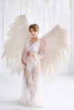 Όμορφο νέο έγκυο κορίτσι με τα μεγάλα φτερά αγγέλου Στοκ φωτογραφία με δικαίωμα ελεύθερης χρήσης