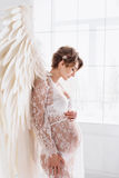 Όμορφο νέο έγκυο κορίτσι με τα μεγάλα φτερά αγγέλου Στοκ Εικόνες