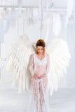Όμορφο νέο έγκυο κορίτσι με τα μεγάλα φτερά αγγέλου Στοκ Φωτογραφία