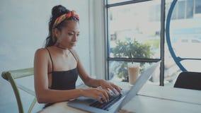 Όμορφο νέο ασιατικό κορίτσι που εργάζεται σε μια καφετερία με ένα lap-top θηλυκό freelancer που εργάζεται στη καφετερία απόθεμα βίντεο