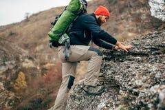 Όμορφο νέο ατόμων οδοιπόρων στα βουνά Οδοιπορία ταξιδιωτικών γενειοφόρος ατόμων κατά τη διάρκεια του ταξιδιού του στοκ εικόνες