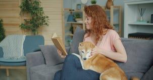Όμορφο νέο βιβλίο γυναικείας ανάγνωσης και λατρευτό σκυλί κτυπήματος στον καναπέ στο εσωτερικό απόθεμα βίντεο