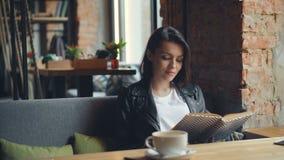 Όμορφο νέο βιβλίο γυναικείας ανάγνωσης στον καφέ που απολαμβάνει τη λογοτεχνία και τη μοναξιά απόθεμα βίντεο